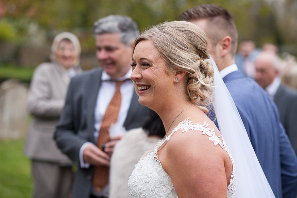 A new bride smiling happily outside a church