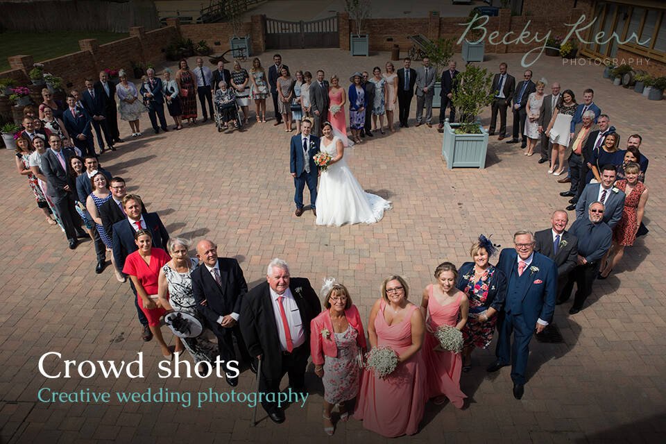 A crowd stood in the shape of a heart as an example of creative wedding photography