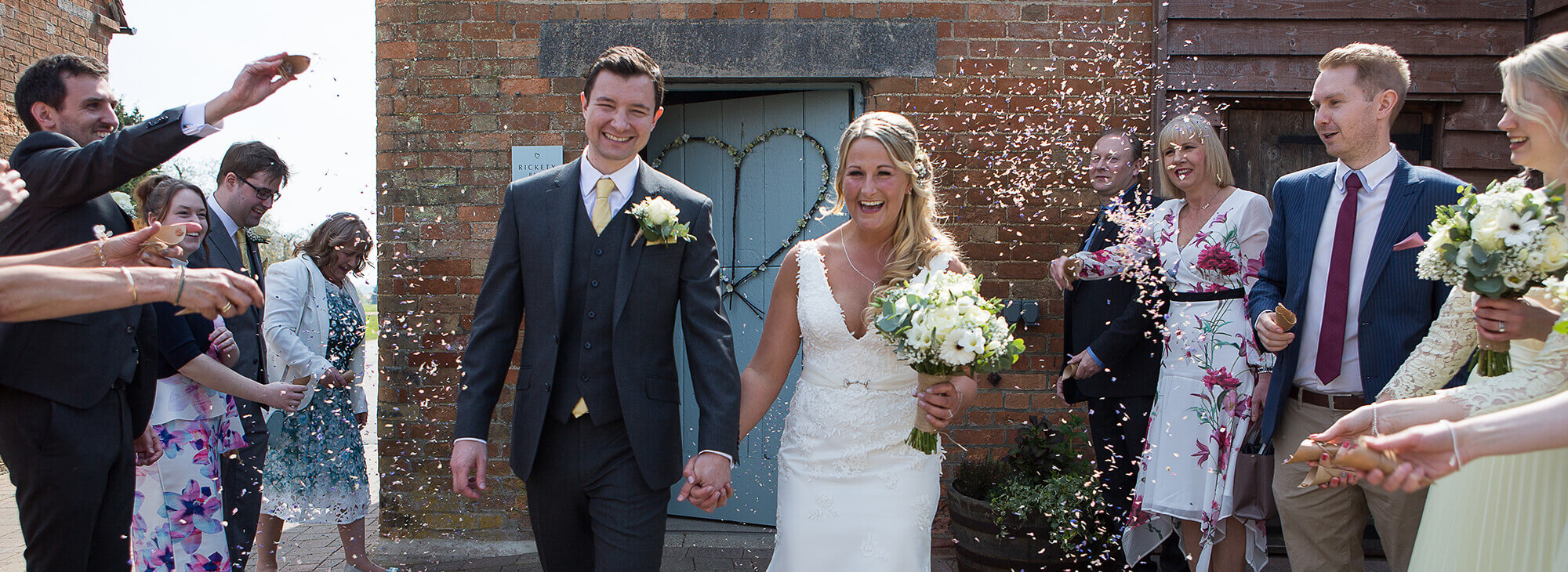 Happy newly married couple smiling after leaving wedding venue
