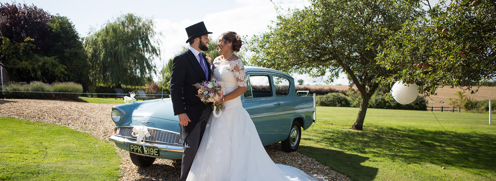 Happy newlyweds smiling in front of vintage car