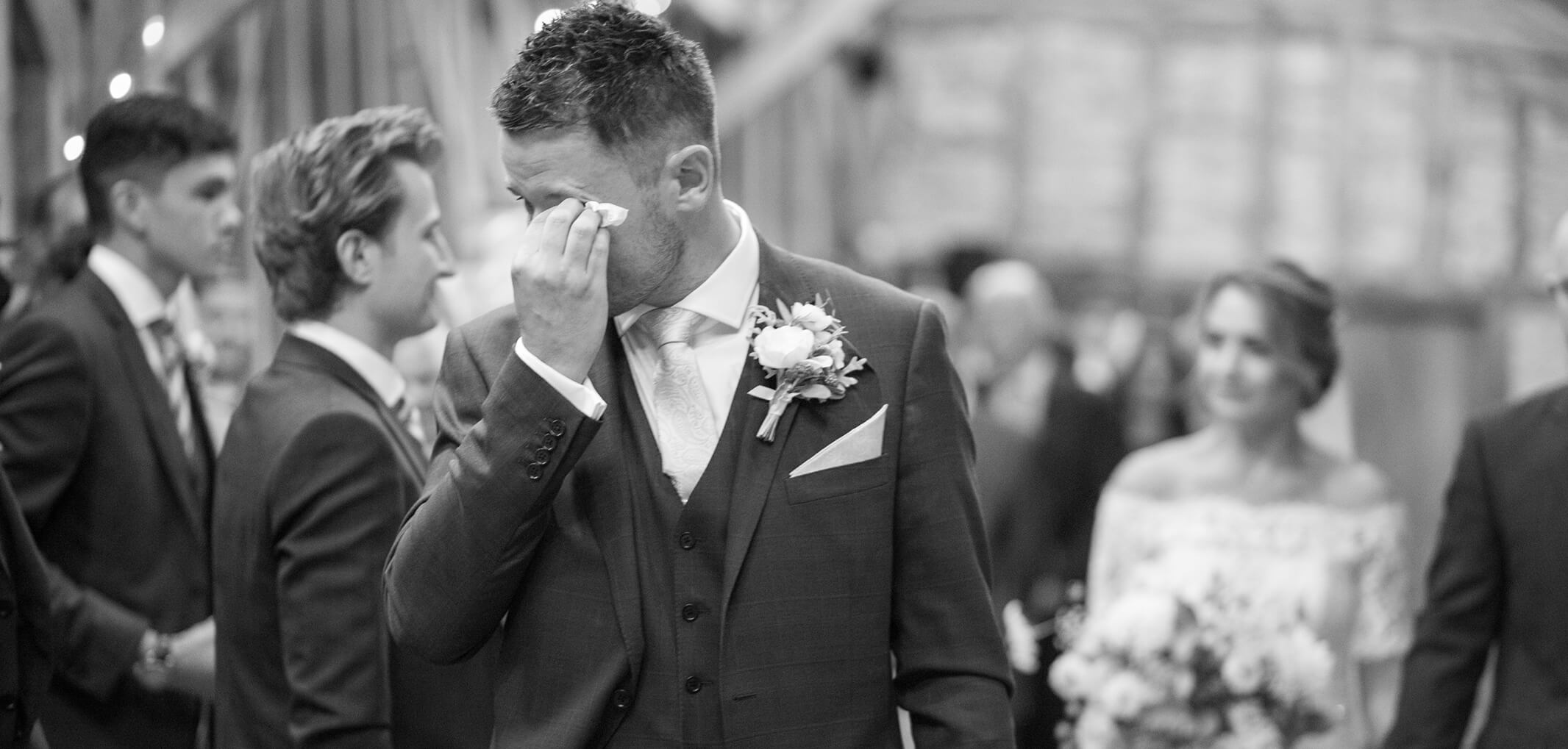A groom wipes away a tear upon seeing his bride walk down the aisle