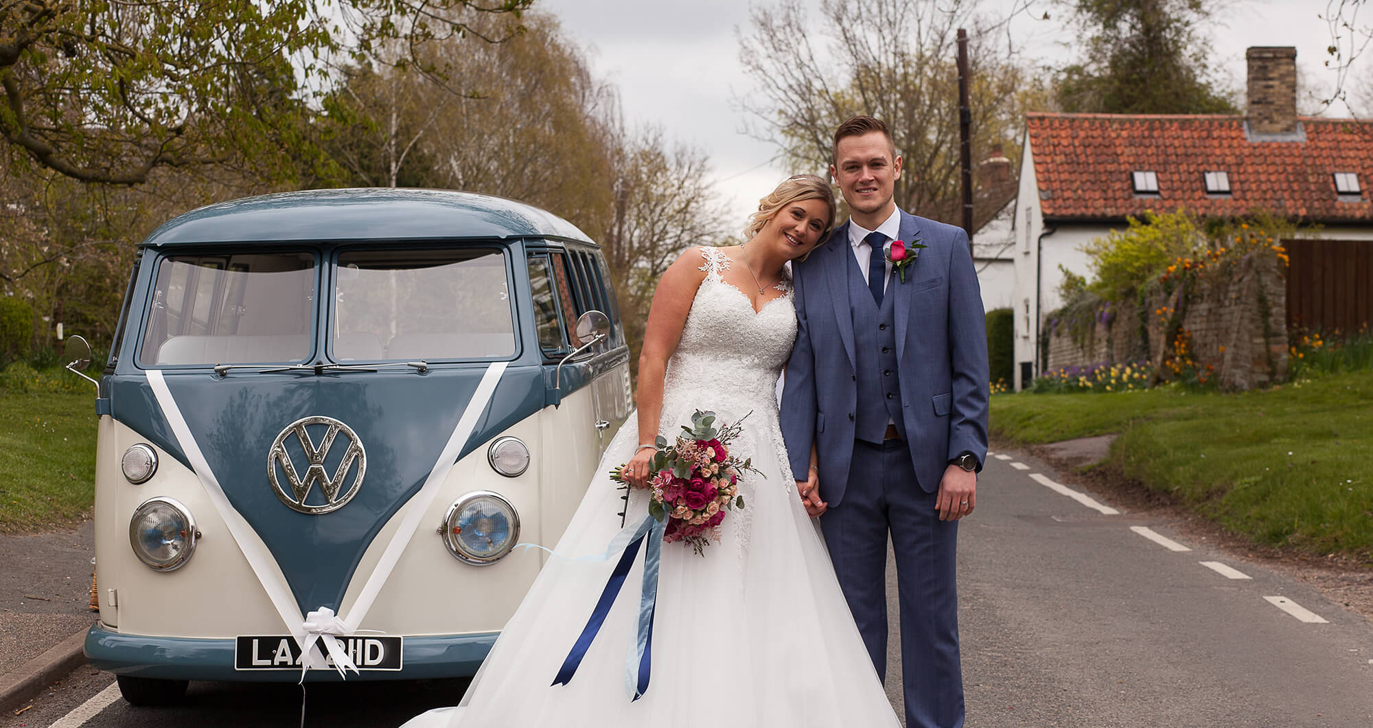A bride and groom standing in front of a VW campervan on their wedding day