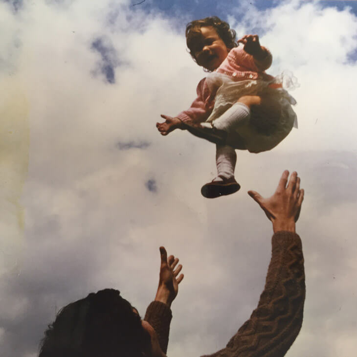 A smiling child being thrown up in the air