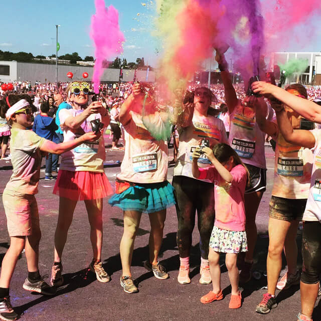 A picture of people throwing coloured powder into the air