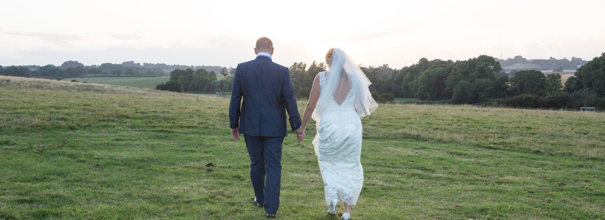 Bride and Groom walking away from the camera in the Northamptonshire countryside