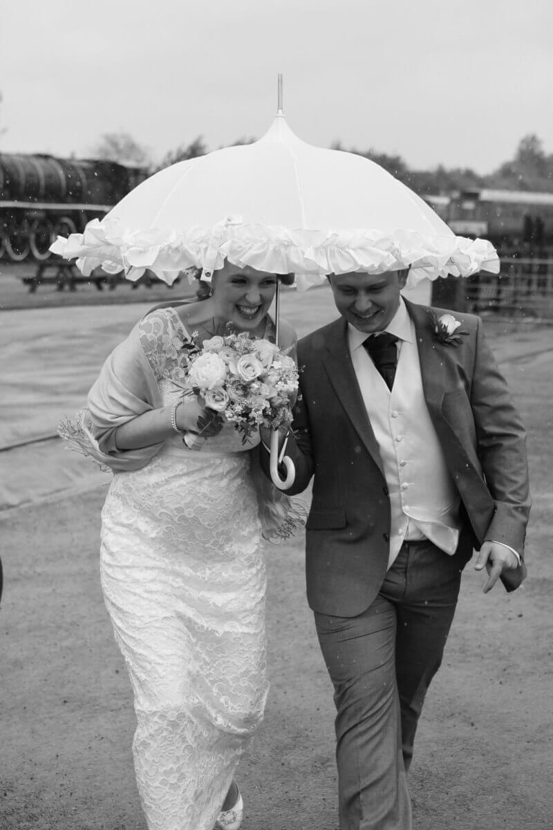 Bride and groom holding a white umbrella