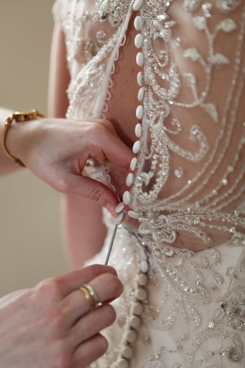 Beautiful lace details and buttons of a cream wedding dress