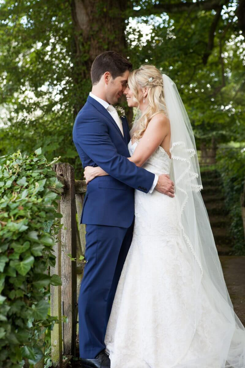 Bride and groom on a bridge at Hexton Mannor Hertfordshire