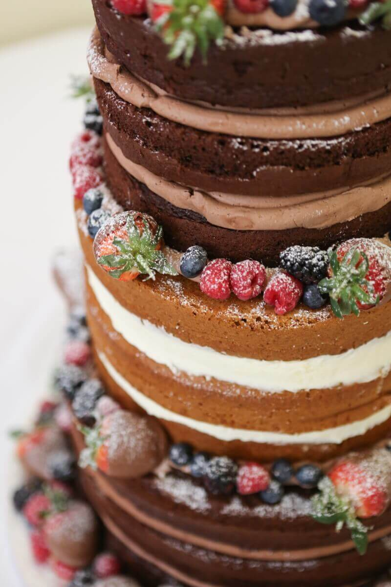 Naked wedding cake with fresh fruit and chocolate.