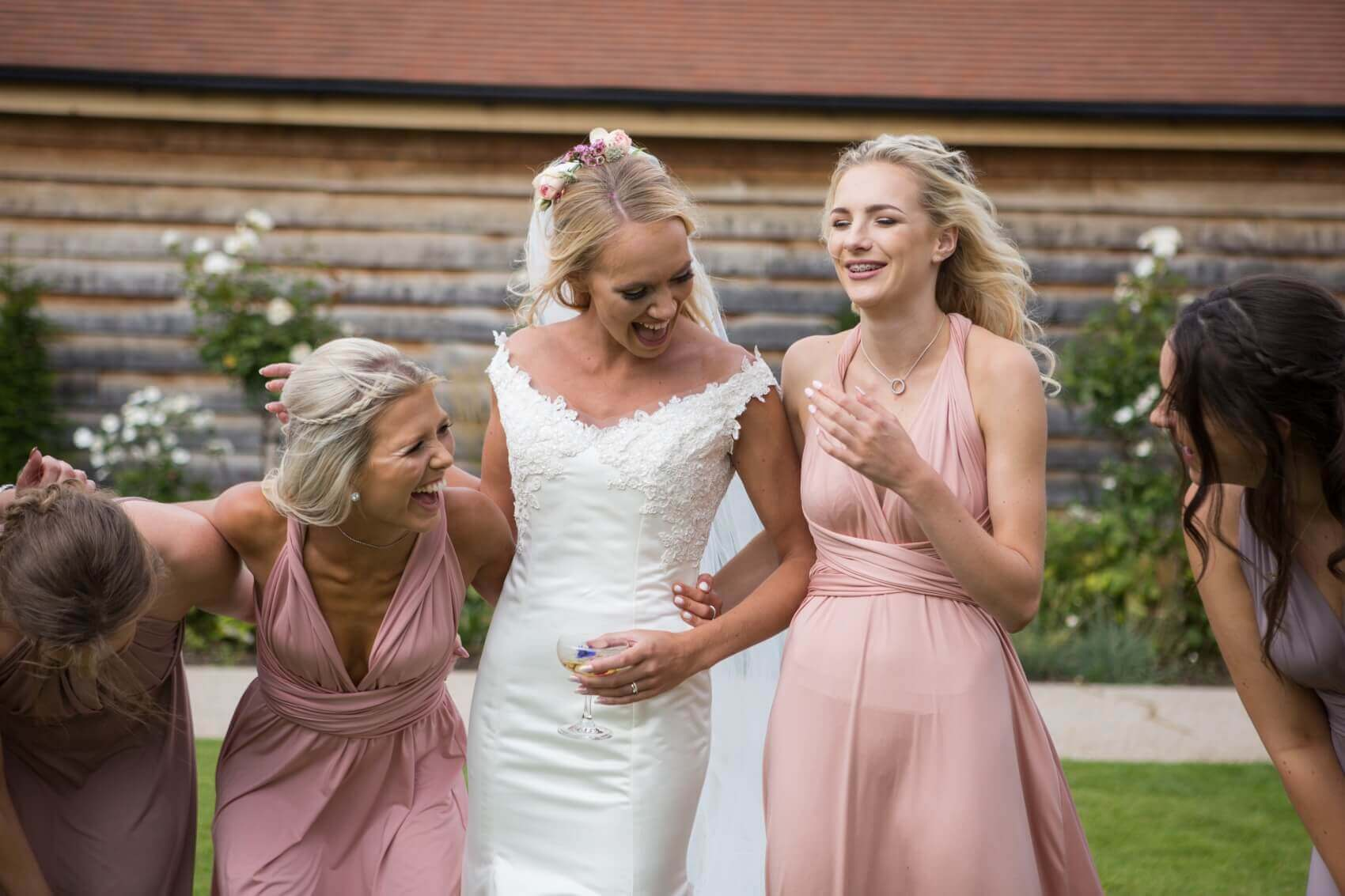 Bride with her bridesmaids laughing in the grounds of Bassmead Manor Farm Barns