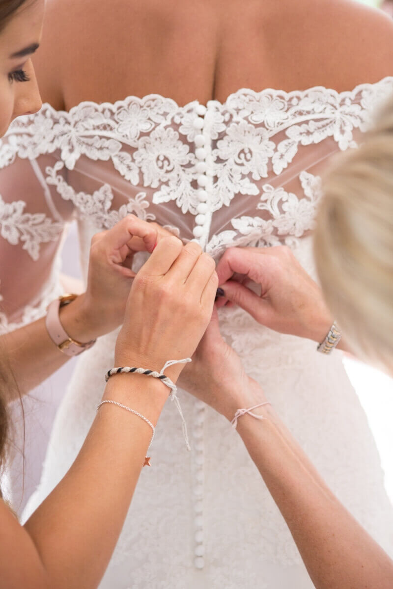 Bride's lace wedding dress being buttoned up