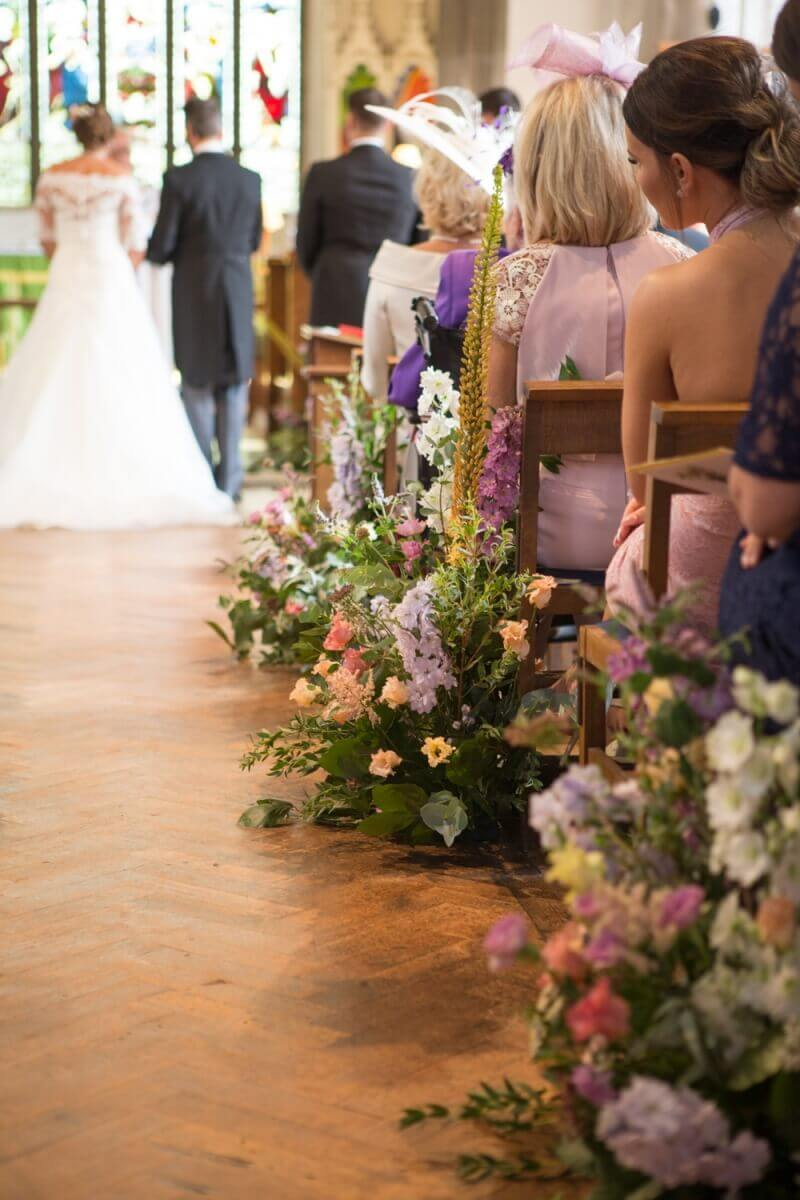 A sea of flowers adorns a church wedding aisle