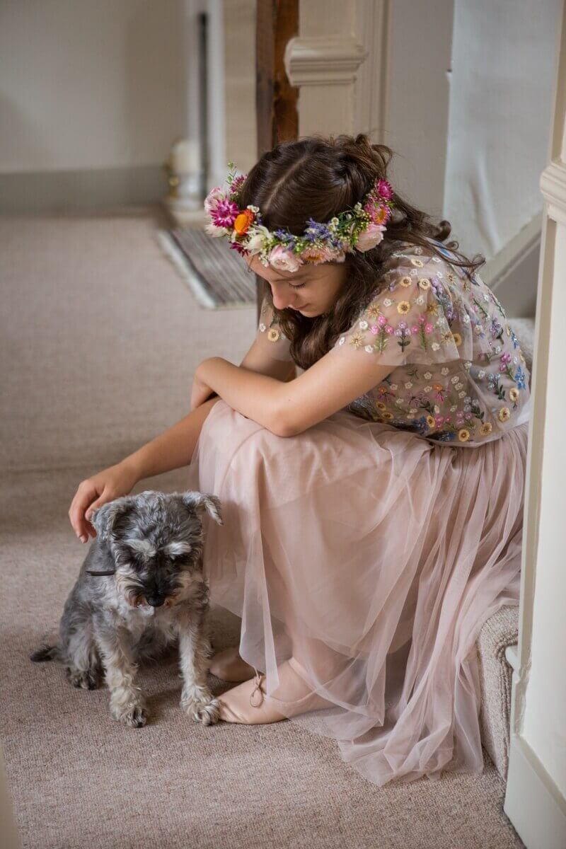 Flower girl in pink with a flower hair crown stroking a dog