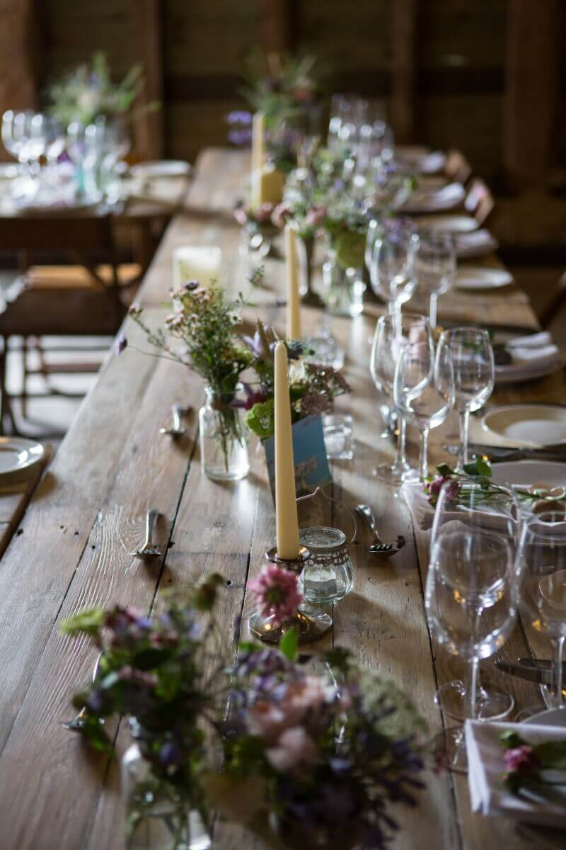 Barn wedding with glasses,flowers and candles on rustic tables