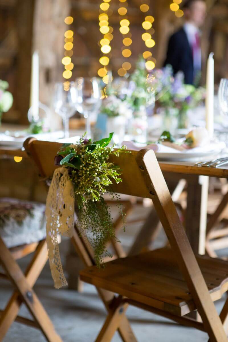 Rustic barn wedding with fair lights and flowers tided to the chairs