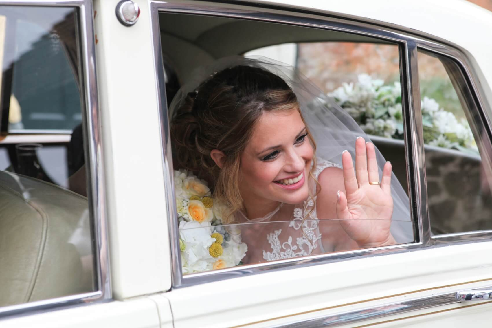 Wedding car with the beautiful bride waving to the guests