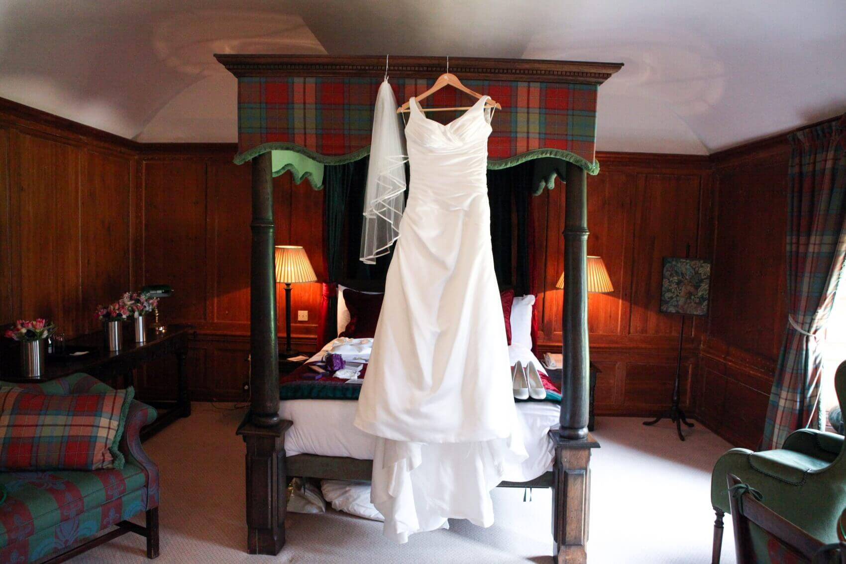 Wedding dress hanging the bed at Flitwick Manor wedding venue